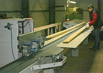 Dva ali trije delavci označujejo napake v lesu, na vhodnem transportnem traku pa se izmeri širina in dolžine letve ter pozicija napak na njej.